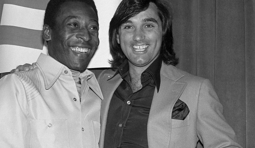 "FILE - An April 7, 1978 file photo showing Pele, left, and former Irish  soccer star George Best, smiling together during an awards luncheon for Pele in Los Angeles. Approaching the tenth anniversary of the death in November 2005, His son Calum is telling the full story of their turbulent father-son relationship for the first time. ""Although he was on this pedestal of being this amazing, iconic footballer, which I will always be proud of, there's a darker side to it,"" he says. ""My dad suffered from a drink problem, which meant we suffered, which meant our relationship suffered.""(AP Photo/George Brich, File)"