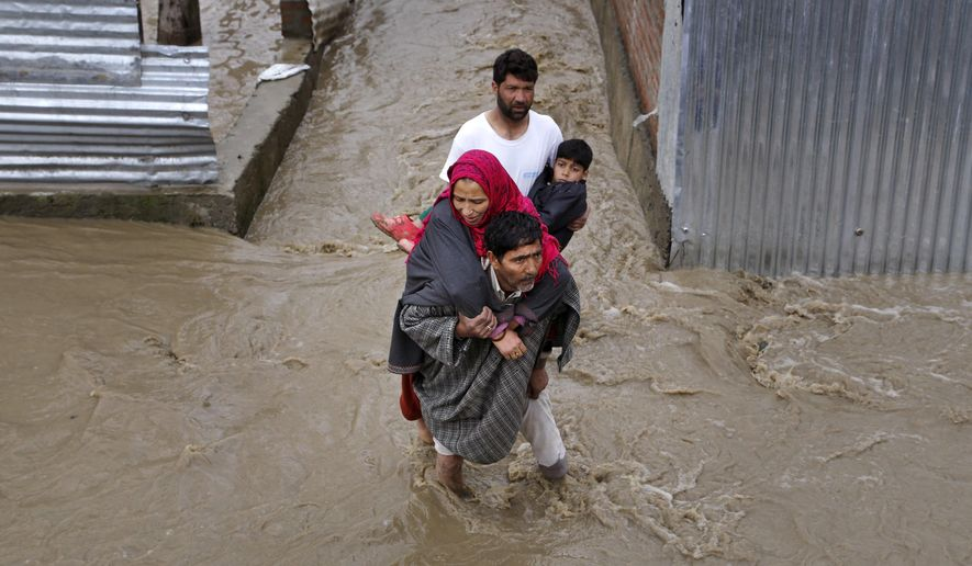 Kashmiri men assist a woman and a child to evacuate from a flooded area in Srinagar, Indian-controlled Kashmir, Monday, March 30, 2015. Authorities in Kashmir issued alerts Monday and asked people to move to higher ground after heavy rain flooded several parts of the Himalayan region. (AP Photo/Mukhtar Khan)