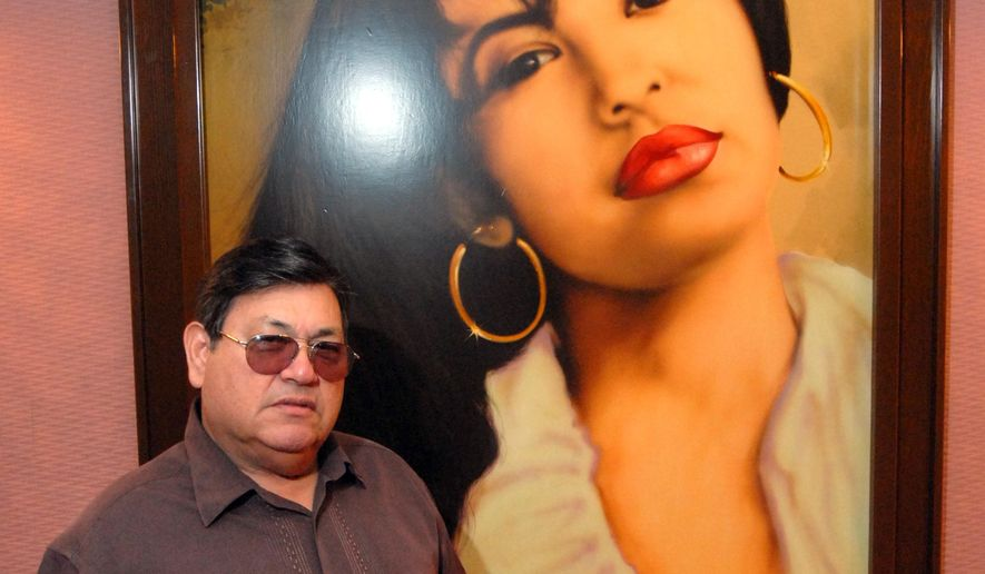 FILE - In this June 24, 2011, file photo, Abraham Quintanilla, the father of the late singer Selena, poses in front of an air brush work of art that a fan gave him after her death, hanging in the studio at Q Productions in Corpus Christi, Texas, where Selena made her last recording. Quintanilla said on Friday, March 27, 2015 that he remembers his daughter every day but he is happy that the world remembers Selena more than ever. (AP Photo/Paul Iverson, File)