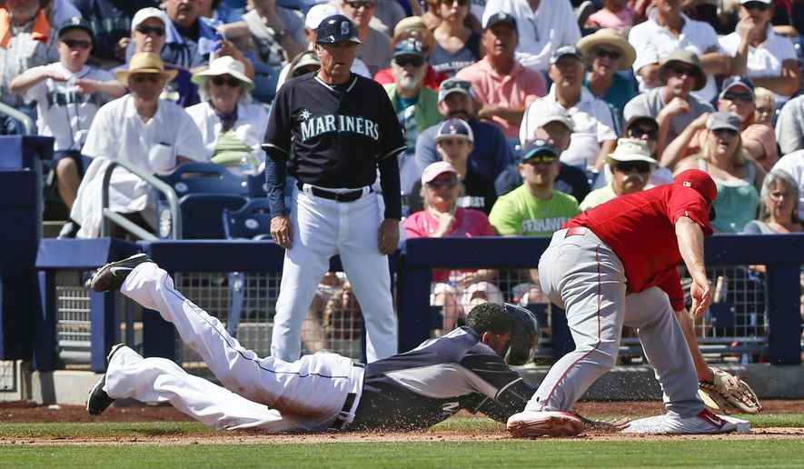 Seattle Mariners' Nelson Cruz dives safely back into third base with no view through his helmet as Los Angeles Angels third baseman David Freese tries to make a tag in the fourth inning of a spring training baseball game Monday, March 30, 2015, in Peoria, Ariz.  (AP Photo/Lenny Ignelzi)