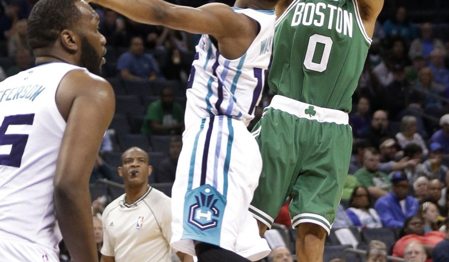 Boston Celtics' Avery Bradley, right, shoots over Charlotte Hornets' Kemba Walker, left, during the first half of an NBA basketball game in Charlotte, N.C., Monday, March 30, 2015. (AP Photo/Chuck Burton)
