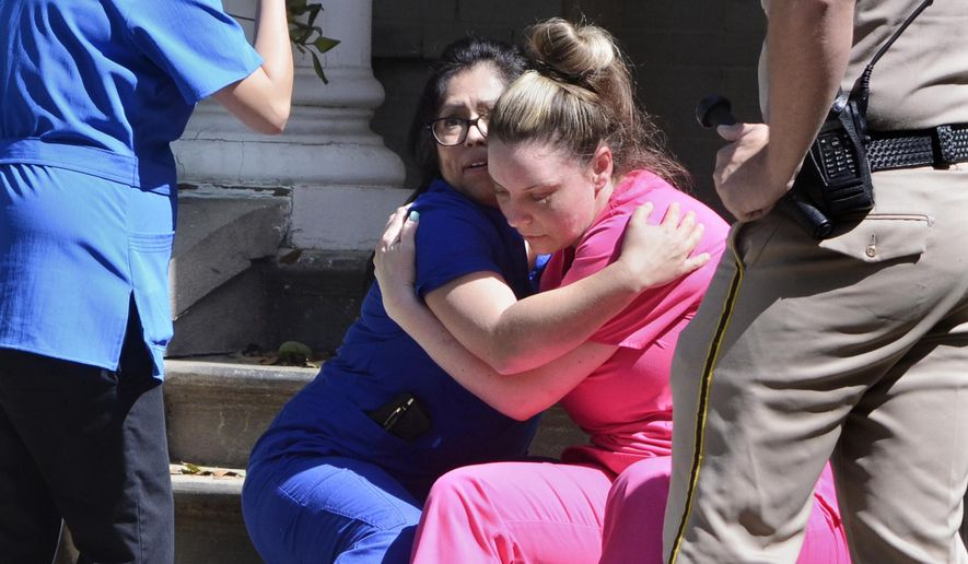 Medical personnel comfort each other after being evacuated by Fresno Police at the scene of a shooting at a medical clinic Tuesday, March 31, 2015, in Fresno, Calif. A man and a woman were found dead after a shooting at the Eye Medical Clinic in downtown Fresno, police in central California said. (AP Photo/The Fresno Bee, John Walker)