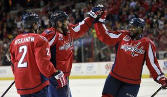 Washington Capitals left wing Alex Ovechkin, center, of Russia, celebrates his goal against the Carolina Hurricanes with Matt Niskanen (2) and Joel Ward, right, during the first period of an NHL hockey game, Tuesday, March 31, 2015, in Washington. It was Ovechkins' 50th goal of the year. (AP Photo/Nick Wass)