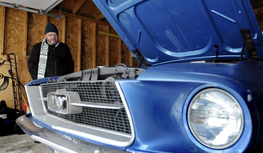 In this Feb. 20, 2015 photo, Kankakee Public Library director Steve Bertrand talks about his 1967 blue convertible Ford Mustang at his garage in Kankakee, Ill. Bertrand said he named the car Millie after his late mother who was nicknamed by school children when she worked in the lunch programs at the Bourbonnais Upper Grade Center and Noel LeVasseur Elementary School. (AP Photo/The Daily Journal, Tiffany Blanchette)