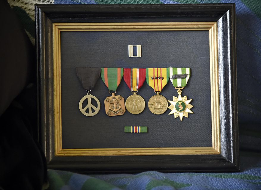 In this photo taken on Monday, March 30, 2105, framed medals from Phillip Hays' U.S. Navy career, are displayed at his home in Corvallis, Ore. The peace sign medal,left, was crafted by the men in Hays' unit to commemorate a time and place significant to them. (AP Photo/The Corvallis Gazette-Times, Andy Cripe)