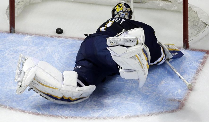 St. Louis Blues goalie Brian Elliott watches as a puck shot by Vancouver Canucks' Nick Bonino slips into the net for a goal during the second period of an NHL hockey game Monday, March 30, 2015, in St. Louis. The Canucks won 4-1. (AP Photo/Jeff Roberson)