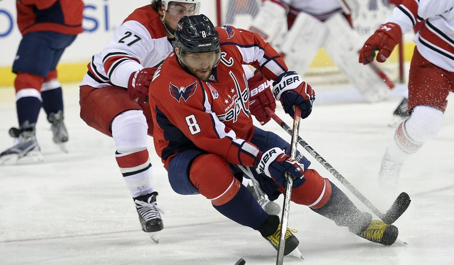 Washington Capitals left wing Alex Ovechkin (8), of Russia, skates with the puck against Carolina Hurricanes defenseman Justin Faulk (27) during the second period of an NHL hockey game, Tuesday, March 31, 2015, in Washington. (AP Photo/Nick Wass)