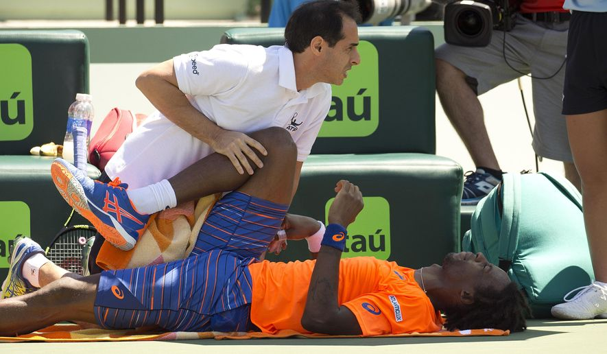 CORRECTS DAY AND DATE - Gael Monfils, of France, get medical attention during his match against Tomas Berdych at the Miami Open tennis tournament in Key Biscayne, Fla., Tuesday, March 31, 2015. (AP Photo/J Pat Carter)