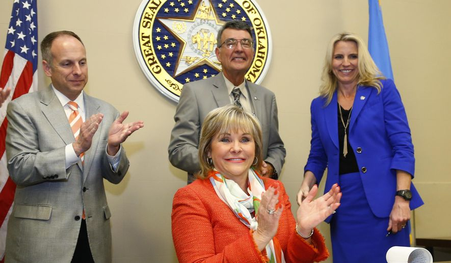 Oklahoma Governor Mary Fallin, bottom, applauds after signing a bill requiring doctors in Oklahoma to check a new prescription drug database before prescribing certain addictive drugs, in Oklahoma City, Tuesday, March 31, 2015. Looking on are Oklahoma House Speaker Jeffrey Hickman, left, R-Fairview, state Rep. Doug Cox, center, R-Grove, and state Sen. A.J. Griffin, R-Guthrie. It the first bill she has signed this legislative session, and it will take effect Nov. 1. (AP Photo/Sue Ogrocki)