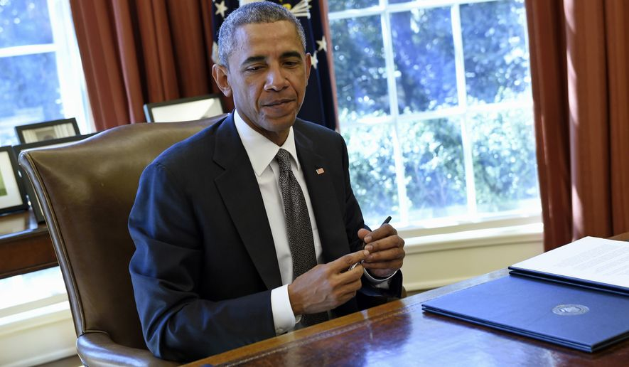 President Barack Obama pauses in the Oval Office of the White House in Washington, Tuesday, March 31, 2015, after signing a Memorandum of Disapproval Regarding S.J. Res. 8, a Joint Resolution providing for congressional disapproval of the rule submitted by the National Labor Relations Board relating to representation case procedures. (AP Photo/Susan Walsh)
