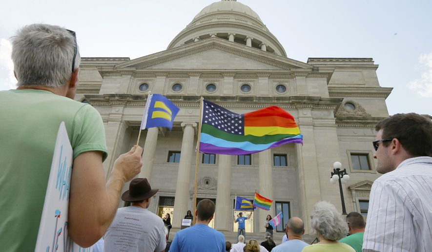 Demonstrators attend a rally on the steps of the Arkansas state Capitol in Little Rock, Ark., Tuesday, March 31, 2015, in protest of a bill that passed in the state House that critics say will lead to discrimination against gays and lesbians. (AP Photo/Danny Johnston)