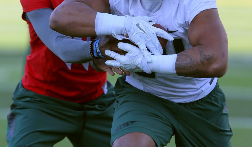 Running back Thomas Tyner takes a handoff from quarterback Travis Jonsen during the University of Oregon opening day of college football spring practice at the Hatfield-Dowlin Complex in Eugene, Ore. Tuesday, March 31, 2015. (AP Photo/The Register-Guard, Brian Davies)