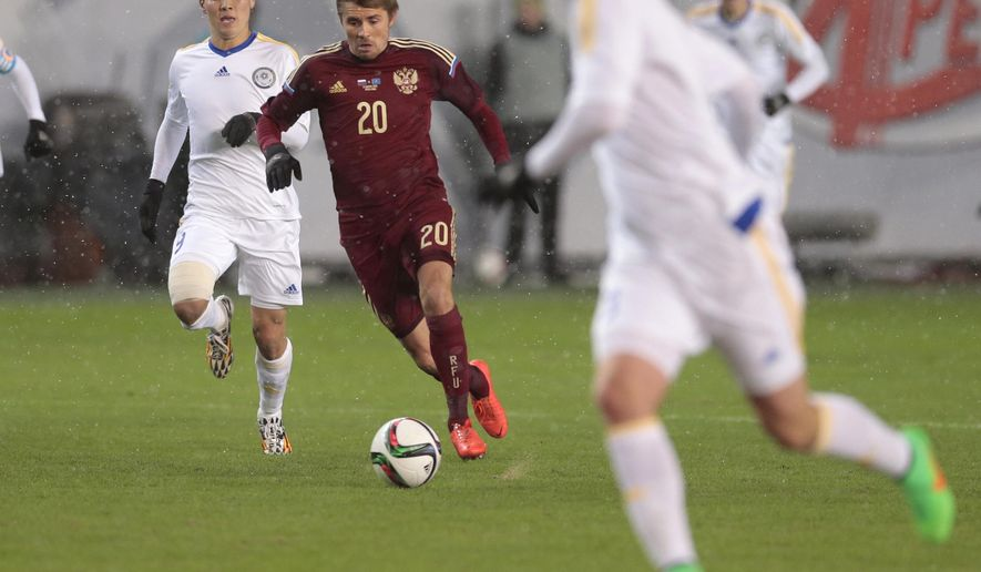 Russia's Dmitry Torbinsky, center, controls the ball in front of Kazakhstan's Bauyrzhan Islamkhanov, left, during their friendly soccer match against  at the Arena Khimki stadium in Moscow, Russia, Tuesday, March 31, 2015. (AP Photo/Ivan Sekretarev)
