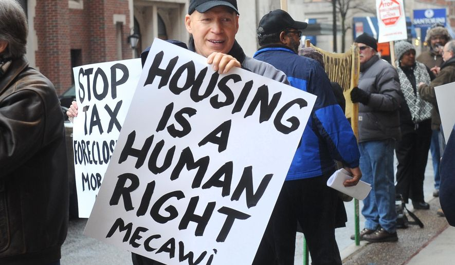 Protestor Henry Cole holds a sign outside the Wayne County Treasurer's office in Detroit on Tuesday March 31, 2015. More than 13,000 Detroit-area property owners have entered into payment plans hoping to avoid losing their homes to tax foreclosure, but another 16,000 living in their homes have yet to take advantage of the offer ahead of Tuesday's deadline. (AP Photo/Detroit News, Max Ortiz)  DETROIT FREE PRESS OUT; HUFFINGTON POST OUT