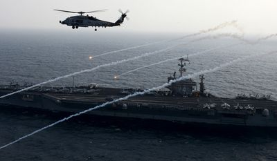 An MH-60R Sea Hawk from the Raptors of Helicopter Maritime Strike Squadron (HSM) 71 launches flares alongside the aircraft carrier USS John C. Stennis (CVN 74). U.S. Navy photo.