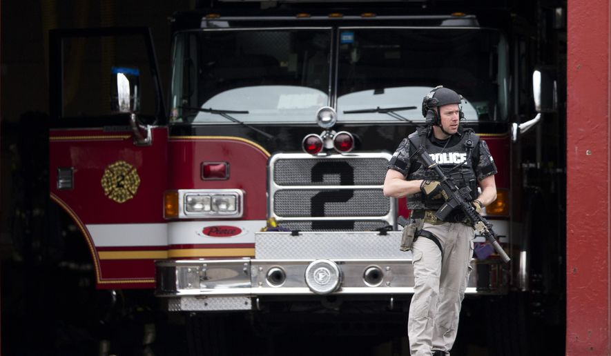 An officer walks out of the LaMott Fire Company after police escorted a man away, Tuesday, March 31, 2015, in Elkins Park, Pa. Authorities say a former volunteer firefighter held four firefighters hostage at the Philadelphia-area firehouse before surrendering to police. No injuries were reported. (AP Photo/Matt Rourke)