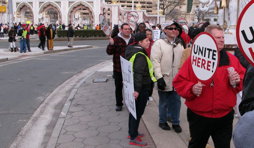 """This March 13, 2015 photo shows union president Bob McDevitt, right, marching during union picketing of the Trump Taj Mahal Casino Resort to protest cuts made by its owners to employee benefits. On Monday, March 30, 2015, McDevitt accused billionaire Carl Icahn, who is acquiring the Taj Mahal's parent company, of trying to """"disembowel"""" Atlantic City to enrich himself. Trump Entertainment Resorts is blocking the former Showboat casino, in background, from being converted into a college campus of Stockton University. (AP Photo/Wayne Parry)"""
