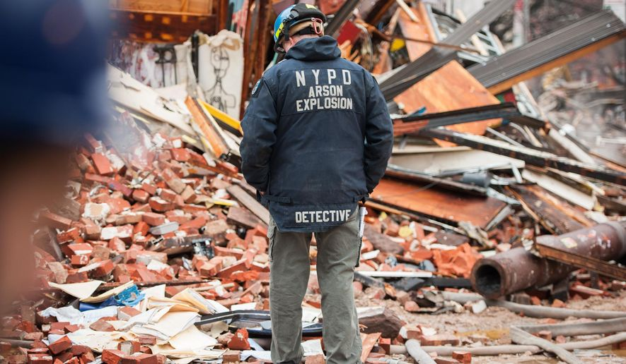 A New York City Police Dept. Arson Explosion detective looks at the site of a building explosion in the East Village neighborhood of New York, Friday, March 27, 2015.  Nineteen people were injured, four critically, after the powerful blast and fire sent flames soaring and debris flying Thursday afternoon.  Preliminary evidence suggested that a gas explosion amid plumbing and gas work inside the building was to blame. (AP Photo/The New York Times, Nancy Borowick, Pool)
