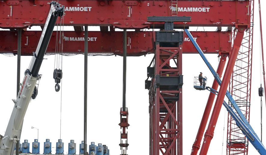 A worker is lifted in a basket toward the top of a crane lifting a 2,000-ton section of a tunnel boring machine out of the ground Monday, March 30, 2015, in Seattle. The machine stalled underground while digging for a planned 1.7-mile tunnel intended to replace Seattle's elevated Alaskan Way Viaduct roadway. The piece being lifted to the surface includes the five-story-tall tunnel cutterhead, motors and the main bearing that will be replaced during the repairs before the piece is lowered back underground to the machine. (AP Photo/Elaine Thompson)