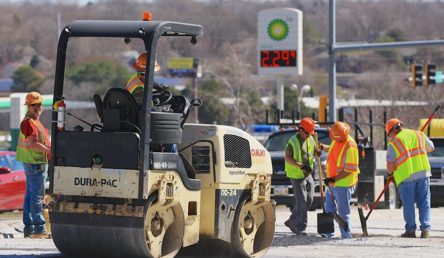 A road crew works on US 275 next to a gas station in Omaha, Neb., Tuesday, March 31, 2015. Nebraska lawmakers will start debate Tuesday on a proposed fuel tax increase that has even won backing from fiscal conservatives who almost never support raising taxes. The proposed 6-cent increase would help pay for roads and bridges. Gov. Pete Ricketts opposes the measure. (AP Photo/Nati Harnik)