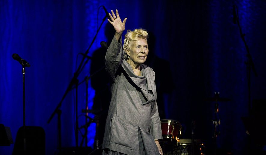 Joni Mitchell waves to the crowd during her 70th birthday tribute concert as part of the Luminato Festival at Massey Hall in Toronto on Tuesday June 18, 2013. Mitchell's website and Twitter account reported Tuesday night March 31, 2015 that she was in the hospital, but gave no details on her condition.  (AP Photo/The Canadian Press, Aaron Vincent Elkaim)