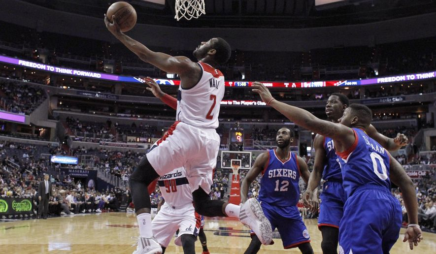 Washington Wizards guard John Wall (2) shoots past Philadelphia 76ers forward Luc Mbah a Moute, (12), center Henry Sims (35) and guard Isaiah Canaan (0) during the first half of an NBA basketball game Wednesday, April 1, 2015, in Washington.  (AP Photo/Alex Brandon)