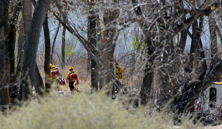 Fire fighters head to battle a grass fire Tuesday, March 31, 2015, in Bosque, N.M. (AP Photo/The Albuquerque Journal, Jim Thompson)