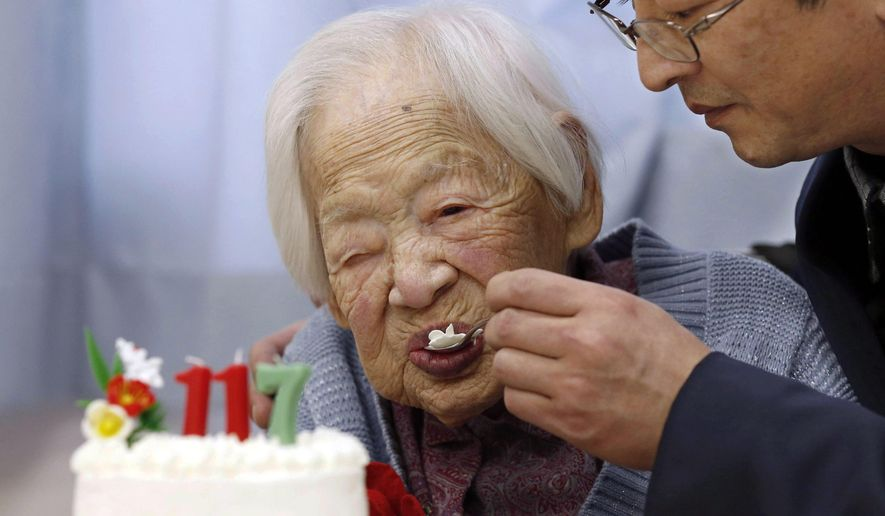 FILE - In this March 5, 2015 file photo, Japan's Misao Okawa who is recognized as the world's oldest living person by Guinness World Records, eats cake, helped by her nursing home staff member, during her 117th birthday celebration event at a nursing home in Osaka, western Japan. Okawa died Wednesday, April 1, 2015, a few weeks after celebrating her 117th birthday. (AP Photo/Kyodo News, File) JAPAN OUT, MANDATORY CREDIT