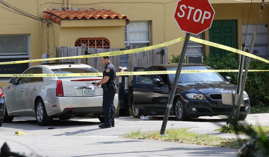 In this photo taken on Monday, March 30, 2015, Miami-Dade police work at a crime scene in Miami, involving the two teenage sons of Roxanne Dube, Canada's counsel general in Maimi.  Germano Wabafiyebazu said their 17-year-old son Jean was killed when he went into a house to buy marijuana, and that police arrested their 15-year-old son Marc. Wabafiyebazu said he and Dube were divorced a few years ago and that their son Jean struggled with substance abuse.  (AP Photo/El Nuevo Herald, Hector Gabino)  MAGS OUT