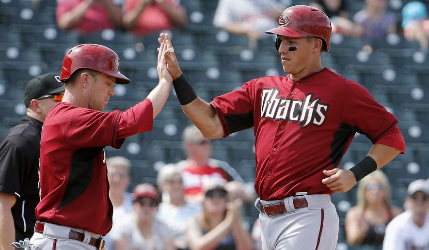 Arizona Diamondbacks' Jake Lamb, right, and Aaron Hill, left, celebrate after both scored runs against the Cincinnati Reds during the fourth inning of a spring training baseball game Wednesday, April 1, 2015, in Goodyear, Ariz. (AP Photo/Ross D. Franklin)