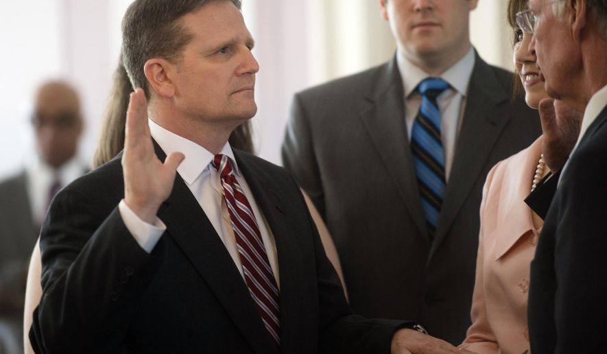 Gov. Robert Bentley, right, swears in Retired Air Force Col. Jeff Dunn as the state's new corrections commissioner in the Old State House Chamber at the Alabama Capitol building Wednesday, April 1, 2015, in Montgomery, Ala. (AP Photo/The Montgomery Advertiser, Albert Cesare)  NO SALES