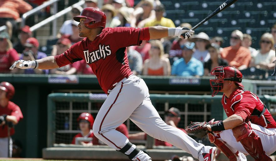 Arizona Diamondbacks' Yasmany Tomas, left, watches the flight of a fly ball to right field as Cincinnati Reds' Devin Mesoraco, right, looks on during the second inning of a spring training baseball game Wednesday, April 1, 2015, in Goodyear, Ariz.  The Reds' Skip Schumaker dropped the fly ball for an error and Tomas ended up at third base, and the Diamondback defeated the Reds 3-0. (AP Photo/Ross D. Franklin)