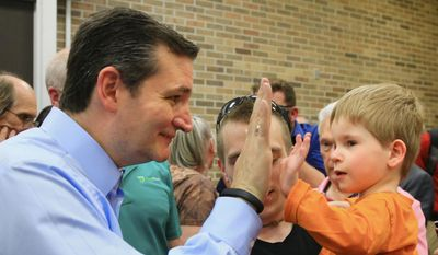 Republican presidential candidate Sen. Ted Cruz, R-Texas, left,  high-fives 4 year-old Wyatt Leeper of Wayne, Neb., following a town hall event at Morningside College in Sioux City, Iowa, Wednesday, April 1, 2015. (AP Photo/Nati Harnik)