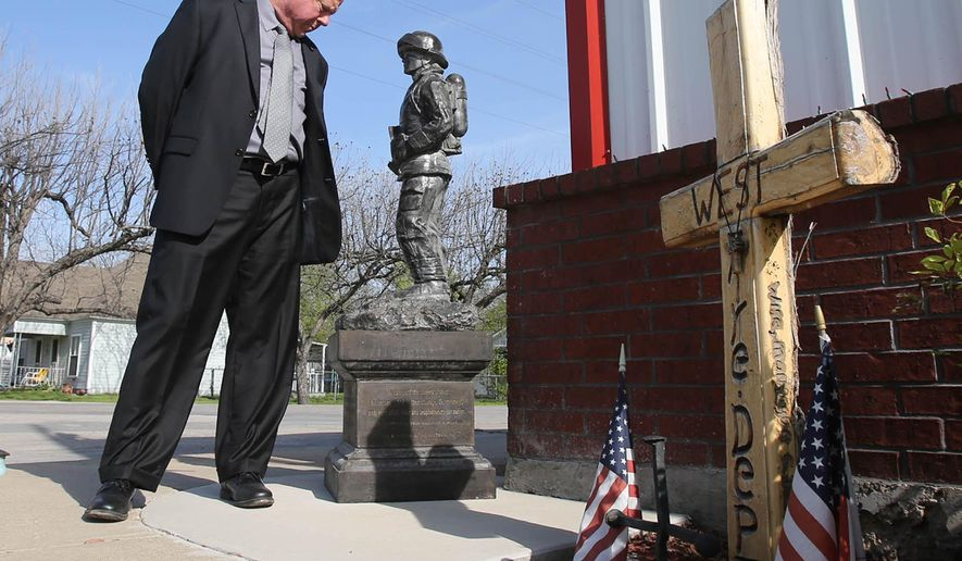 Mayor Tommy Muska looks over a memorial at the volunteer fire department in West, Texas on Tuesday, March 31, 2015. Nearly two years after a fire set off a deadly ammonium nitrate explosion at the West Fertilizer Co., Texas businesses selling the chemical aren't subject to any new laws, and only a handful store it in fireproof buildings as experts recommend, state officials said. (AP Photo/Waco Tribune Herald, Jerry Larson)