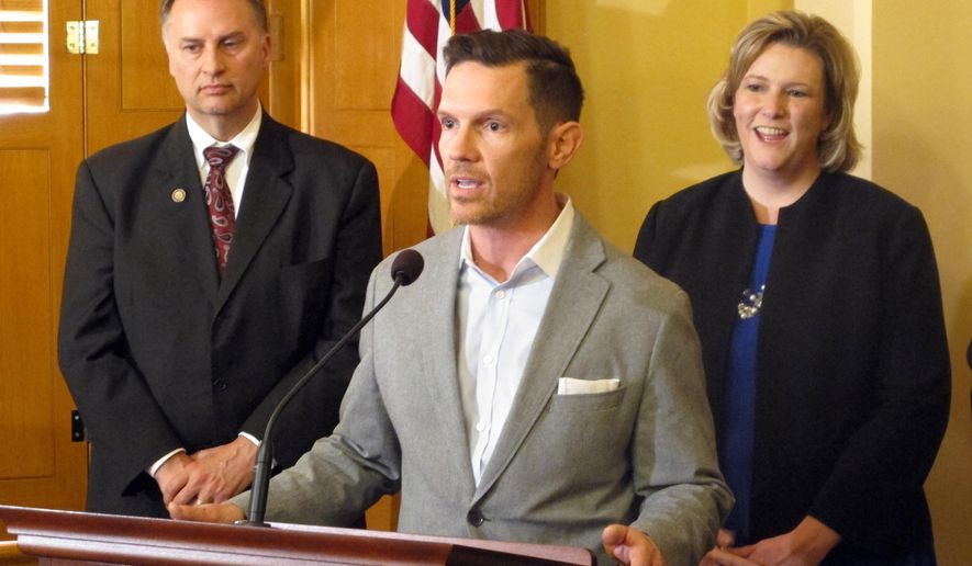 Brent Johnson, owner of a chain of salons in Dayton and Columbus, speaks out against an Indiana law that critics say could permit discrimination against gays and lesbians, as Canton Mayor William Healy, left, and Dayton Mayor Nan Whaley listen in, on Wednesday, April 1, 2015, in Columbus, Ohio. Johnson spoke an event where city officials from around the state encouraged Indiana companies to relocate to Ohio. (AP Photo/Andrew Welsh-Huggins)