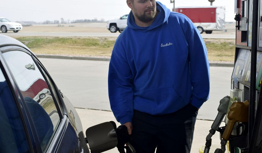 John Sandbulte, of Steen, Minn., fills up his car at the Coffee Cup Fuel Stop in in Brandon, S.D., Wednesday, April 1, 2015. Sandbulte, who commutes to work in Sioux Falls, S.D., said the new 6-cent gas tax hike will help fix ailing roads and bridges in South Dakota. (AP Photo/Kevin Burbach)
