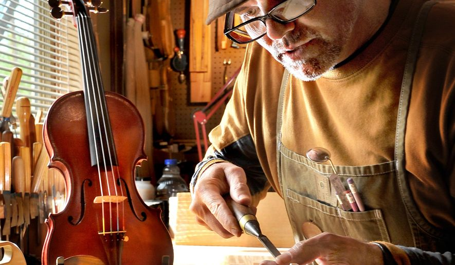 In this photo taken on Monday, March 30, 2015. John Hill, who started making violins and other stringed instruments 17 years ago, works on an instrument in his newly-built studio and shop off Kings Highway in southwest Medford, Ore. (AP Photo/The Medford Mail Tribune, Bob Pennell)