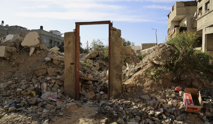 "An empty frame doorway is seen standing on the rubble of a destroyed building that was damaged in last summer's Israel-Hamas war, without a door painting, presumably painted by British street graffiti artist Banksy, east of Jebaliya, in the northern Gaza Strip, Tuesday, March 31, 2015. Artworks by the elusive British graffiti artist Banksy are typically sold for hundreds of thousands of dollars, but in the Gaza Strip a local painter has succeeded in purchasing a Banksy original for less than $200. The popular street artist is believed to have sneaked into Gaza in February, leaving behind four murals including one drawn on a metal door that depicted a Greek goddess cowering against the rubble of a destroyed house. The painting of the goddess Niobe, titled ""Bomb Damage,"" was drawn on the lone remaining part of a two-story house belonging to the Dardouna family in Jabaliya, northern Gaza Strip. (AP Photo/Adel Hana)"