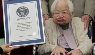 In this  Feb. 27, 2013, file photo, Japan's Misao Okawa, then 114, poses with the certificate of the world's oldest woman, which was presented to her by Guinness World Records Japan Country Manager Erika Ogawa, unseen, at a nursing home in Osaka, western Japan. The world's oldest person has died nearly a month after celebrating her 117th birthday. Her nursing home says Misao Okawa died of heart failure early Wednesday, April 1, 2015. (AP Photo/Itsuo Inouye, File)