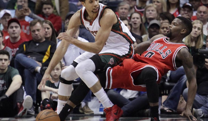 Milwaukee Bucks guard Michael Carter-Williams, left, drives into Chicago Bulls guard Aaron Brooks during the first half of an NBA basketball game Wednesday, April 1, 2015, in Milwaukee. (AP Photo/Darren Hauck)