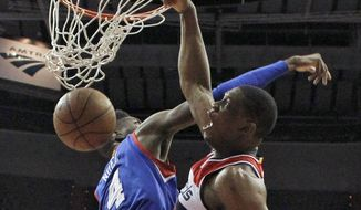 Washington Wizards center Kevin Seraphin (13) dunks against Philadelphia 76ers center Nerlens Noel (4) during the first half of an NBA basketball game Wednesday, April 1, 2015, in Washington.  (AP Photo/Alex Brandon)