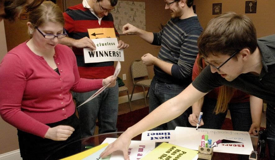 In this Feb. 14, 2015 photo, from left, Becky Nicol, Chris Lukeman, Andrew Christensen and Keith Hollenkamp pick word phrases for celebration photos after completing a team building exercise in a puzzle room at Escape Bloomington in Bloomington, Ill. (AP Photo/The Pantagraph, Carlos T. Miranda)