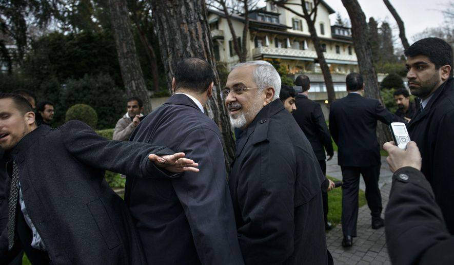 Iranian Foreign Minister Javad Zarif, centre, talks to members of the media while walking through a courtyard at the Beau Rivage Palace Hotel during an extended round of talks, Wednesday, April 1, 2015 in Lausanne, Switzerland. Negotiations over Iran's nuclear program appeared headed for double overtime on Wednesday, beset by competing claims after diplomats abandoned a March 31 deadline for the outline of a deal and agreed to press on. (AP Photo/Brendan Smialowski, Pool)
