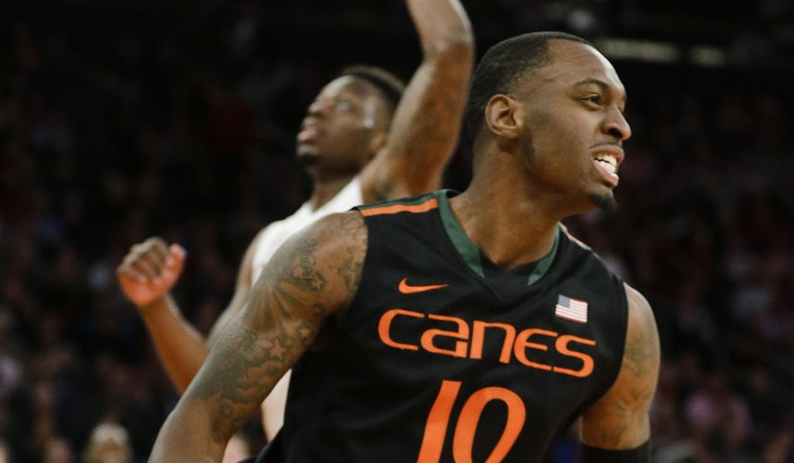 Miami's Sheldon McClellan (10) reacts after scoring as Temple's Quenton DeCosey (25) reaches for the ball during the second half of a semifinal at the NIT college basketball tournament Tuesday, March 31, 2015, in New York. Miami won 60-57. (AP Photo/Frank Franklin II)