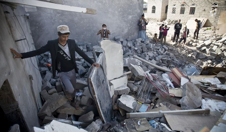 FILE - In this Tuesday, March 31, 2015 file photo, people gather near the rubble of houses destroyed by Saudi airstrikes near the airport in Sanaa, Yemen. Saudi Arabia and its allies plan an ambitious ground offensive on multiple fronts in Yemen. It may be inevitable if they want to defeat Iranian-backed Shiite rebels but it also carries enormous risks, from the inhospitable, mountainous terrain and a possible guerrilla war to al-Qaida militants waiting in the wings. (AP Photo/Hani Mohammed, File)