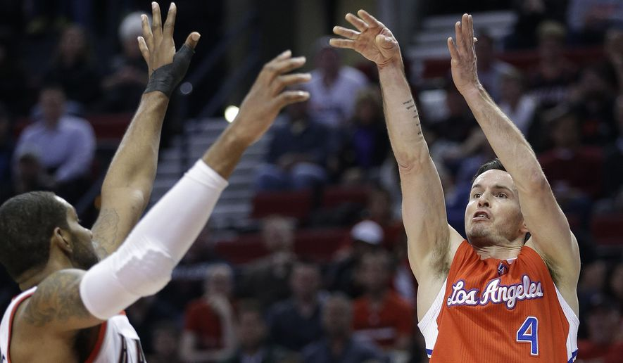Los Angeles Clippers guard J.J. Redick, right, shoots over Portland Trail Blazers forward LaMarcus Aldridge during the first half of an NBA basketball game in Portland, Ore., Wednesday, April 1, 2015.  (AP Photo/Don Ryan)