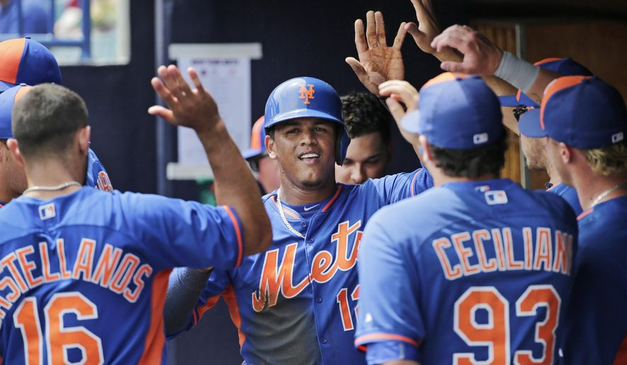 FILE - In this March 25, 2015, file photo, teammates congratulate New York Mets center fielder Juan Lagares after he stole third and scored on a throwing error by New York Yankees catcher John Ryan Murphy in the first inning of an exhibition baseball game in Tampa, Fla. The Mets are working to complete a new contract with Juan Lagares that would guarantee the center fielder $23 million from 2016-19, including a buyout of a $9.5 million option for 2020. (AP Photo/Kathy Willens, File)