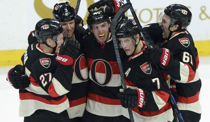 Ottawa Senators' Patrick Wiercioch, middle, celebrates his game winning goal against the Tampa Bay Lightning in overtime of an NHL hockey game, Thursday, April 2, 2015 in Ottawa, Ontario.  (AP Photo/The Canadian Press, Sean Kilpatrick)