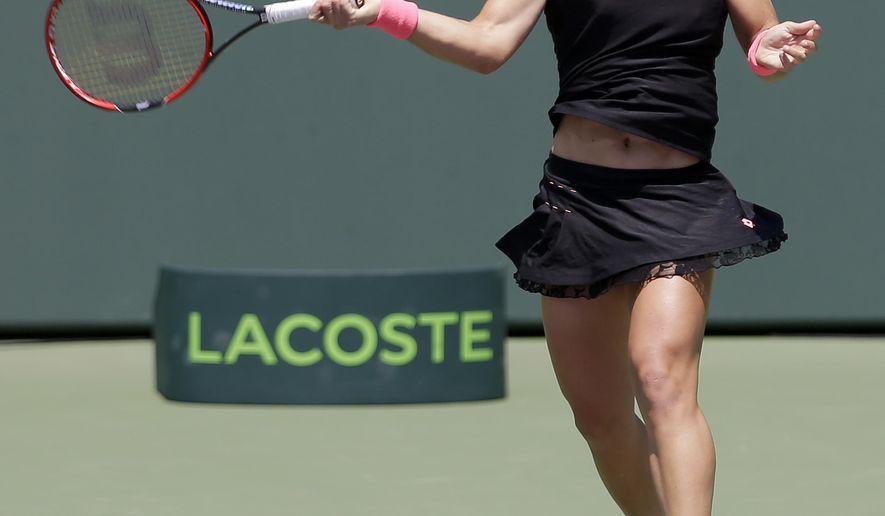 Carla Suarez Navarro, of Spain, returns to Andrea Petkovic at the Miami Open tennis tournament, Thursday, April 2, 2015, in Key Biscayne, Fla. (AP Photo/Alan Diaz)