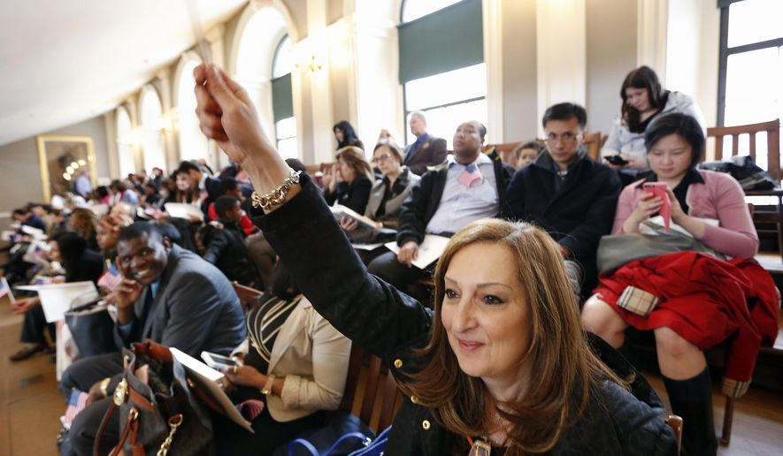 Rima Bechara, lower right, who came from Lebanon, waves to her family in the gallery while waiting to take the oath of U.S. citizenship during a naturalization ceremony in Boston, Thursday, April 2, 2015. Nearly 400 people from dozens of countries ranging from Albania to Zimbabwe took part in the ceremony. (AP Photo/Michael Dwyer)